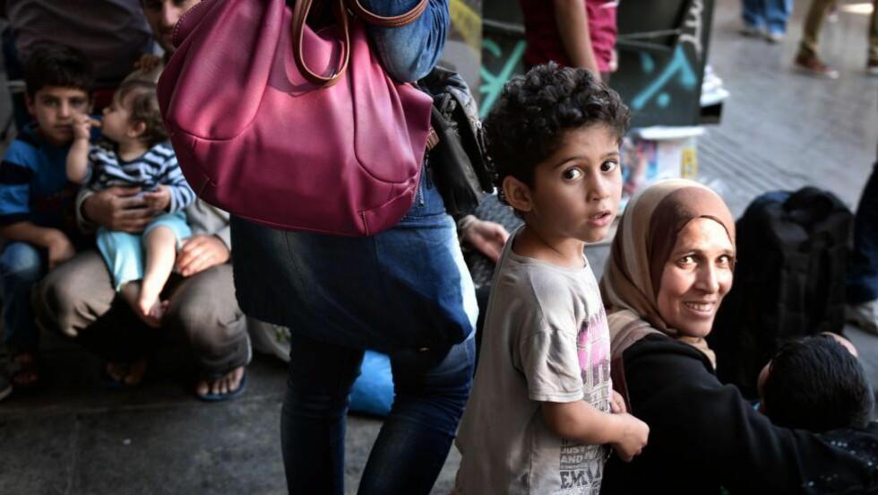 DELER BEFOLKNINGEN:  Avgjørelsen om å ta inn 8000 syriske flyktninger i løpet av tre år har trolig skapt større polarisering i det norske folket. Her sitter syriske flyktninger ved Omonia-torget i Aten 6. juli - kort tid etter å ha kommet til Europa.  Foto: LOUISA GOULIAMAKI/ AFP PHOTO