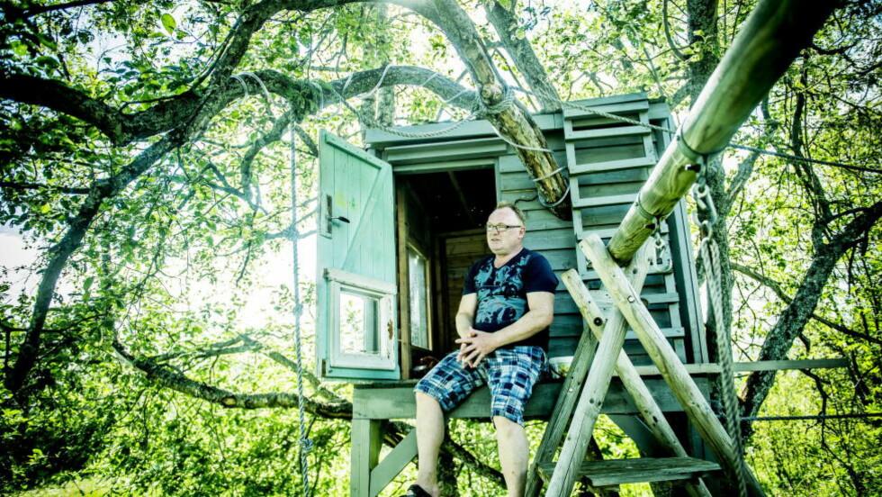PER I HAGEN: Det tok tid å venne seg til stillheten og været på Senja. Første gang Per Sandberg klagde over at det var for kaldt i badevannet, fikk han beskjed om å kjøpe seg en våtdrakt. Her i hytta han og sønnen (9) har bygd i hagen. Foto: THOMAS RASMUS SKAUG