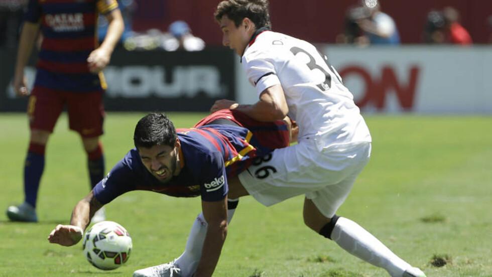 STOPPET: Barcelonas Luis Suarez stoppes av Matteo Darmian. Foto: AP Photo/Jeff Chiu