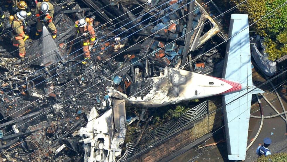TRAFF BOLIGGHUS:  Brannmannskap i Tokyo jobber med å slokke brannen etter at et småfly krasjet i et boligområde søndag formiddag  ved 11-tiden. En kvinne i huset og de to mennene i flyet omkom. Foto: Kyodo/AP/NTB Scanpix.