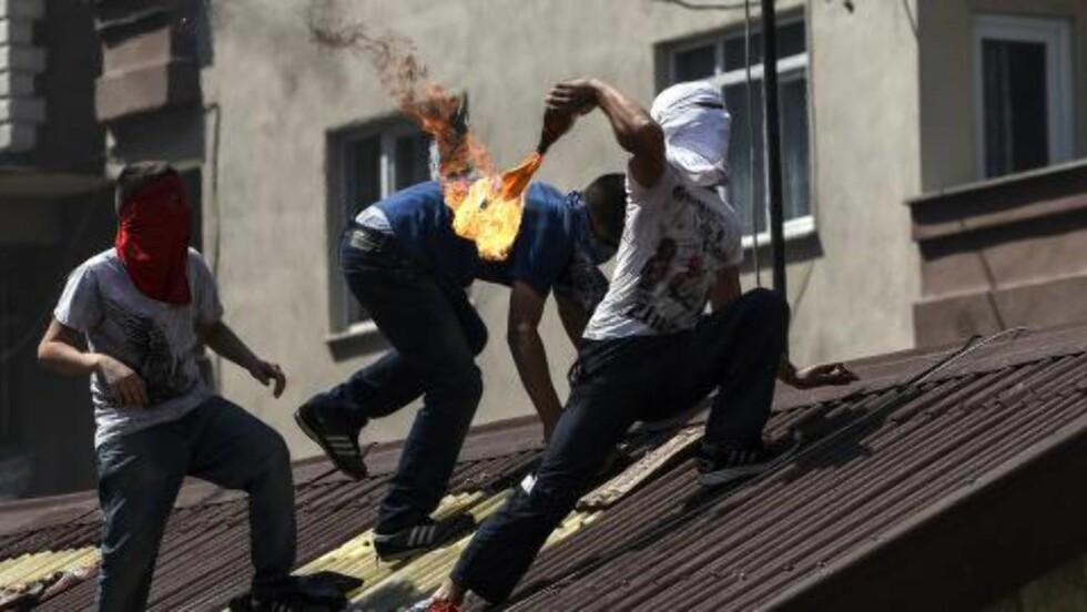 STORE UROLIGHETER:  Etter terrorangrepet mot en ungdomsgruppe i Suruc i Tyrkia på mandag, har det vært store protester mot regjeringen i Tyrkia, blant annet i Istanbul. Her kaster venstreradikale ungdom en molotov-cocktail under sammenstøt med politiet i dag. Foto: Bulent Kilic / AFP Photo / NTB Scanpix