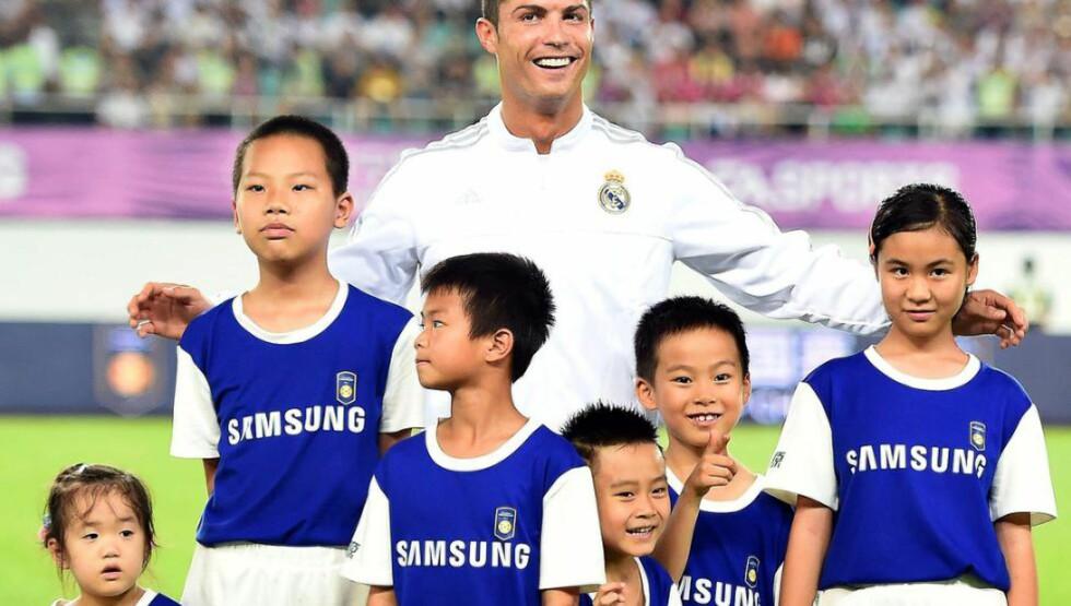 DEN STORE HELTEN: Det er ingen tvil om at Cristiano Ronaldo er vel så populær i Kina som i Spania. Da Real Madrid entret gresset foran en treningskamp i dag, forlot flere av maskotene sin utdelte spiller og stilte seg sammen med Ronaldo. Foto: EPA/XI YA CHINA OUT