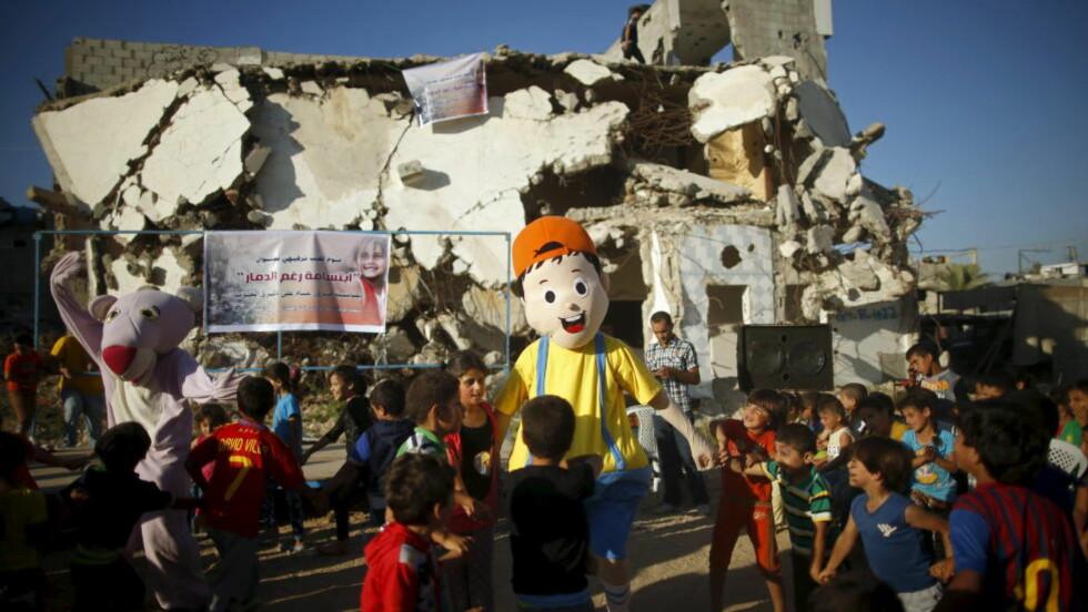 SMIL: Kostymekledde palestinere underholder barn på Gazastripen. I bakgrunnen et hus som ble ødelagt under krigen i fjor sommer. En stor andel  av barna orådene som ble hardets rammet avkrigen sliter med mareritt, sengevæting og andre tegn på traume. Bildet er tatt tidliger ei juli.Foto: REUTERS/Mohammed Salem/ NTB Scanpix