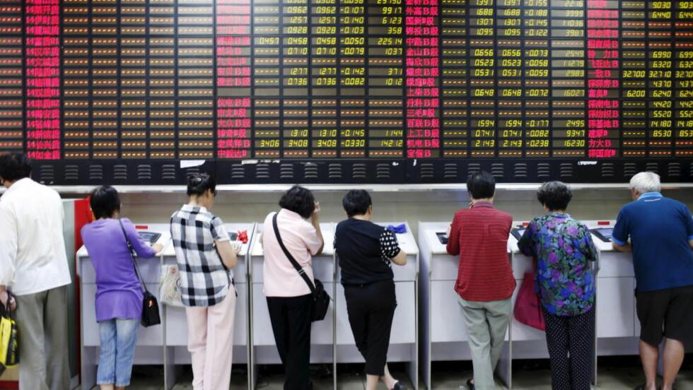 AVVENTER:  Potensielle investorer ved skranken i et meklerhus i Shanghai tidligere i juli for studere prospekter og kursutviklingen. Merk at seks av åtte potensielle børskunder her er kvinner. Foto: Aly Song, Reuters/NTB Scanpix.