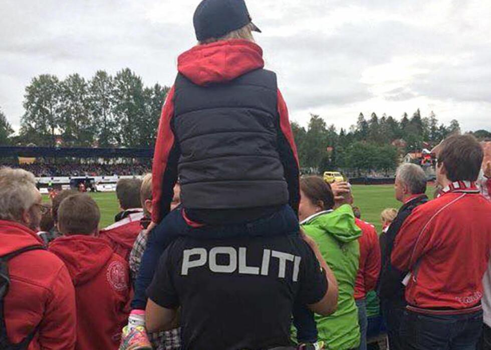 SÅ LITE: Da politiet i Follo oppdaget at den unge Brann-supporteren ikke så noe av kampen, fikk hun plass på skuldrene til politibetjenten. Foto: Follo politidistrikt