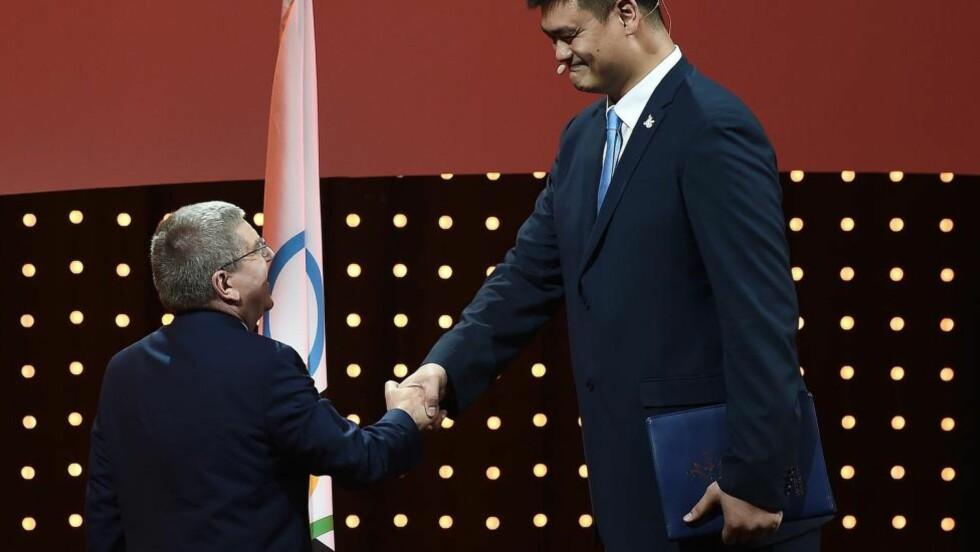FORMIDABELT TRØKK:  Kina har puttet mye politisk prestsisje inn i forsøket på å få vinter-OL 2022. Her er det tidligere basketstjerne Yao Ming i den kinesiske OL-delegasjonen som overleverer søknaden til IOC-president Thomas Bach. For ordens skyld; også Bach er en storvokst mann. FOTO:AFP / Manan Vatsyayana.