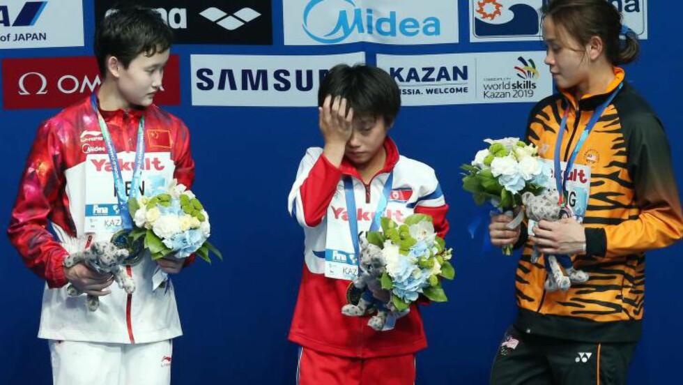 TØRKER TÅRER: Gullvinneren tørker tårer på podiet, mens sølvvinner Ren Qian (t.v) og Pandela Rinong ser på. Foto: AFP PHOTO / ROMAN KRUCHININ / NTB Scanpix