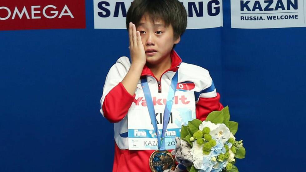 RØRT: 16 år gamle Kim Kuk-hyang ble svært rørt da nasjonalsangen ble spilt til ære for henne - etter å ha tatt Nord-Koreas første gull i svømme-VM. Foto: AFP PHOTO / ROMAN KRUCHININ / NTB Scanpix
