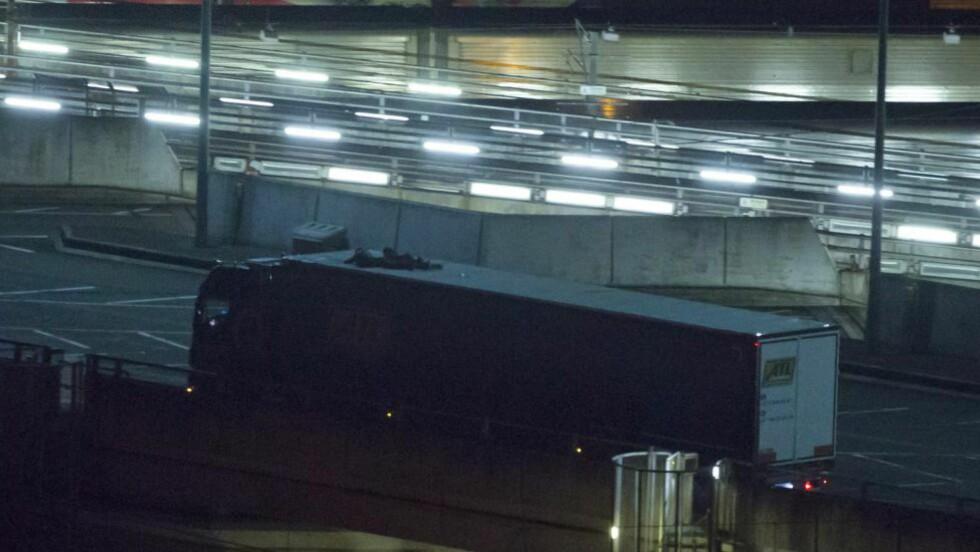KLAMRER SEG FAST: Gjennom dødens tunnel klamrer flyktninger seg fast til drømmen om et bedre liv i Storbritannia.  Fredag ble 200 flyktninger stoppet av fransk politi i havnebyen Calais. Dette bildet er tatt på britisk side av Calais-tunnelen, og de to flyktningene har dermed klart å ta seg fra «The jungle», forbi gjerder, politi og sniffende hunder. Foto: AFP PHOTO / JUSTIN TALLIS