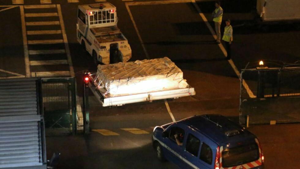 TIL FRANKRIKE: Politiet eskorterte vrakresten til et fly på øya Réunion for å få den fraktet til Toulouse i Frankrike. Der skal etterforskere og spesialister fra Boeing granske delen fra en flyvinge ned til de minste detaljer. AFP PHOTO / RICHARD BOUHET