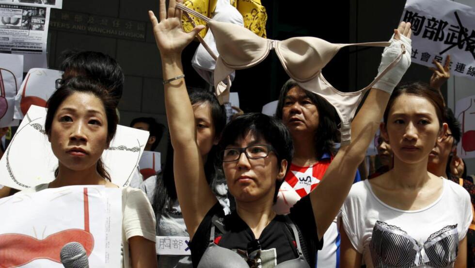 DEMONSTRERTE:  Rundt 100 mennesker tok til gatene i Hongkong søndag etter at en kvinne ble fengslet av politiet. Foranledningen skal være at den fengslede skal ha angrepet en politibetjent med sine bryster.  REUTERS/Liau Chung-ren