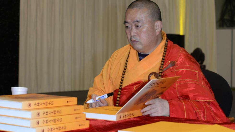 TJENER PENGER: Shi Yongxin signerer bøker under den årlige Shaolin-festivalen i London. Nå etterforskes han for underslag og seksuelle relasjoner til flere forskjellige kvinner. Foto: NTB Scanpix