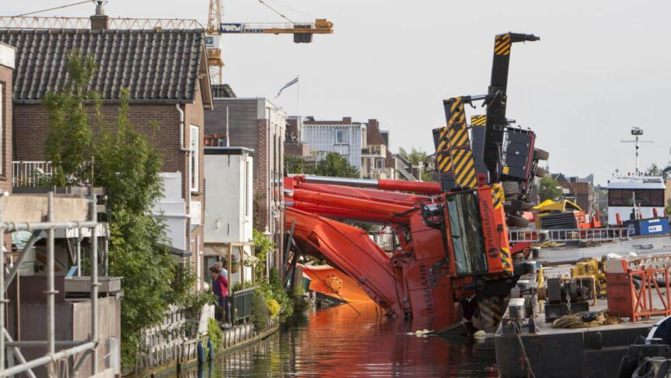 To kraner som løftet et bruelement veltet mandag i den nederlandske byen Alphen aan den Rijn. Minst 20 mennesker ble skadd i ulykken. Foto: Ronald Fleurbaaij / Reuters / NTB Scanpix