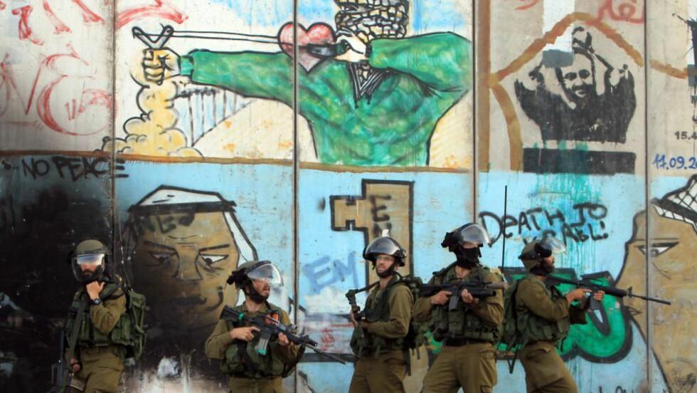 KLARE FOR KAMP:  Israelske soldater står foran en grafitti som er laget på den kontroversielle muren mellom Ramallah og Jerusalem på Vestbredden i fjor sommer. Palestinere på Vestbredden protesterte mot den voldsomme bombingen av Gaza, og ble blant annet møtt av disse soldatene. Foto: Abbas Momani / Afp / Scanpix