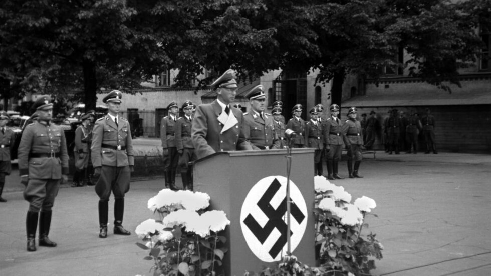 NAZISYMBOLIKK: Få uker etter at tyskerne invaderte Norge, ble Hitlers venn Josef Terboven sendt til Norge som rikskommisær. Han styrte landet med dikatoriske fullmakter i fem år, men var også kjent for sine ville fester på kronsprinsgården Skaugum - nazistenes høyborg i Norge. Her taler han i forbindelse med overrekkelsen av den militære utmerkelsen Jernkorset til to fra Det tyske sikkerhetspoliti på Majorstuen skole i Oslo, juni 1942.  Foto: NTB Scanpix