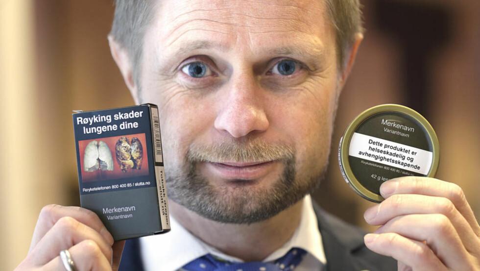 HELSEMINISTER: Helse- og omsorgsminister Bent Høie (H) med forslagene til de ny innpakningene til snus og tobakkspakker, på en pressekonferanse om forebyggende tiltak på tobakksområdet. Foto: Vidar Ruud / NTB scanpix