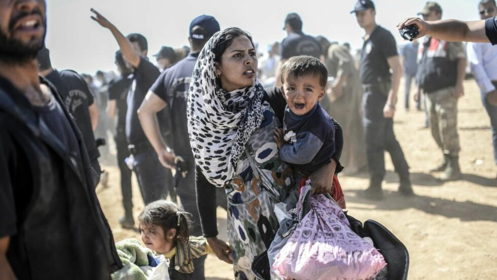 <strong>PÅ FLUKT:</strong> En kurdisk kvinne fra Syria krysser grensa til Tyrkia sammen med sine barn i september i fjor. Foto: Bulent Kilic/AFP