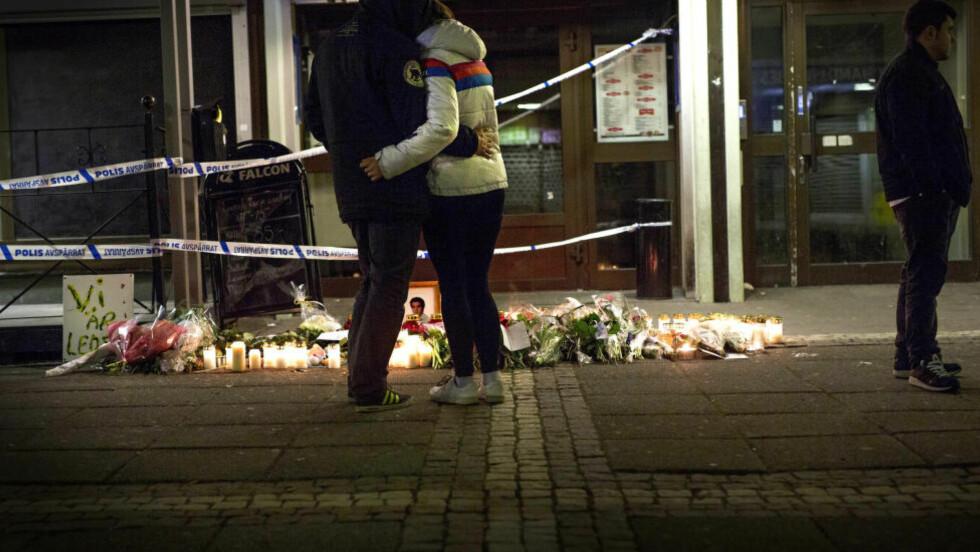 ÅSTEDET:Det er kveld, og de aller fleste er gått hjem. Lysene blinker i mørket og det er satt opp et bilde av en av ofrene for skuddvekslingen sent onsdag kveld. Foto: Anita Arntzen / Dagbladet