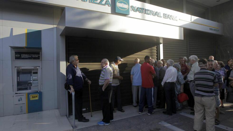 <strong>VENTER:</strong> Grekere, mange av dem pensjonister uten minibankkort, samles utenfor en bankfillial i Aten i dag tidlig. Hellas har innført kapitalkontroll og stenging av banker for å unngå økonomisk kollaps. Foto: EPA/ORESTIS PANAGIOTOU