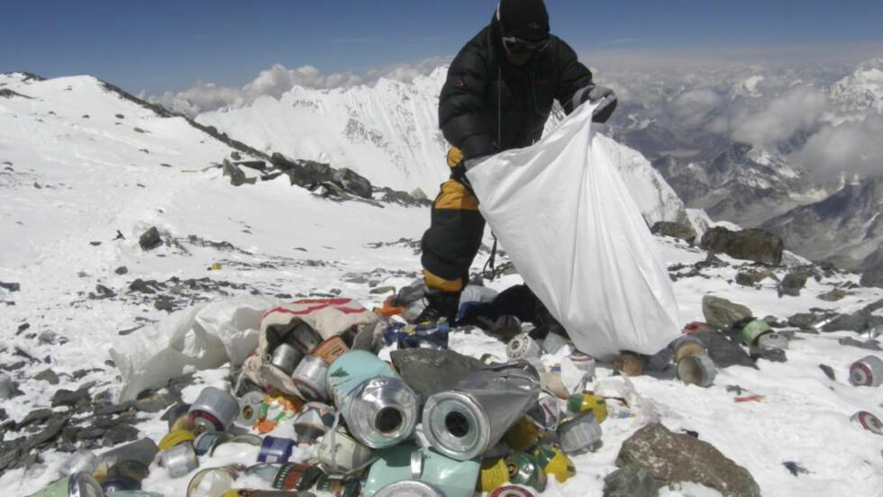 SØPPELFYLLING: Langs ruten fra den nederste campen og opp til toppen av Mount Everest ligger det igjen både telt, soveposer, oksygentanker, tauverk, stiger, matbokser og lik etter klatrere som aldri kom seg ned. Dette bildet fra mai 2010 viser en nepalsk sherpa som plukker søppel på 8000 meters høyde. Foto:  AFP PHOTO/Namgyal SHERPA