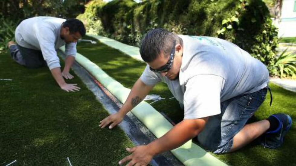 PLASTPLEN: Noen tar ansvar som følge av tørken. Her legges det ned kunstgress i en hage i Burlingame i California. Foto: Justin Sullivan/Getty Images/AFP