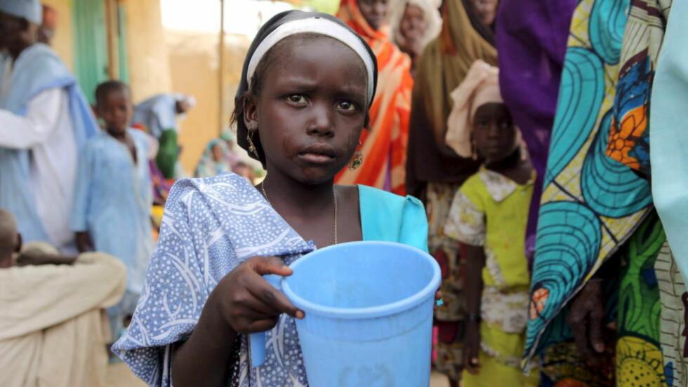HERJER: En jente holder en bøtte med vann hun har fått av nigerianske regjeringssoldater som deler ut mat og tepper i Damasak i Nigeria. Flere hundre tusen barn er hardt rammet av ekstremistgruppa Boko Harams herjinger i Nigeria. Foto: Reuters / NTB scanpix