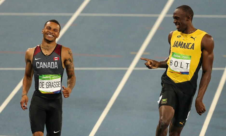 GLISTE OG LO: Bolt begynte å slakke av litt på slutten, og ble nesten tatt igjen av kanadiske Andre de Grasse, som satte personlig rekord. Det ville ikke Bolt ha noe av, og de to smilte og lo under løpet. Foto: Salih Zeki Fazlioglu / Anadolu Agency / NTB scanpix