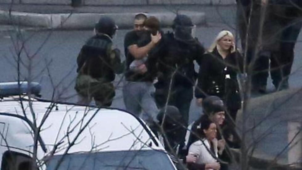 GISLER:  En rekke gisler tas hånd om av politiet etter de aksjonerte mot kosher-butikken. Foto: AFP Photo / Thomas Samson.