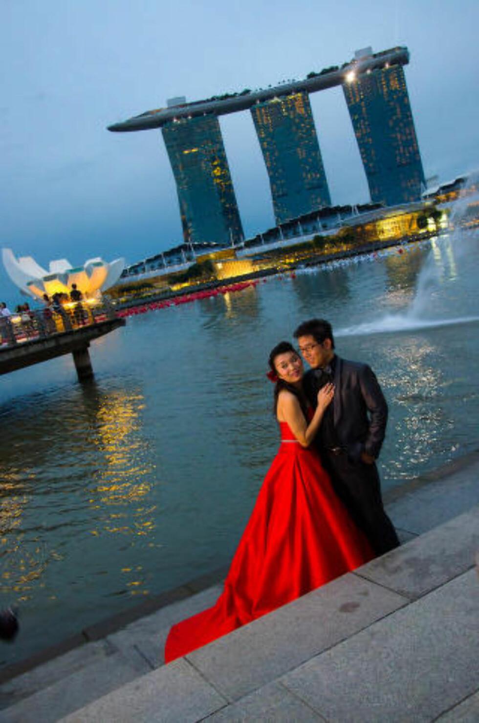 RØD FOR KJÆRLIGHET: I Singapore er det vanlig å ta bryllupsbildene sine en helt annen dag enn på selve bryllupsdagen. Vi fikk bli med på bryllupsfotografering med det imponerende bygningskomplekset Marina Bay Sands i bakgrunnen. Foto: MARI BAREKSTEN