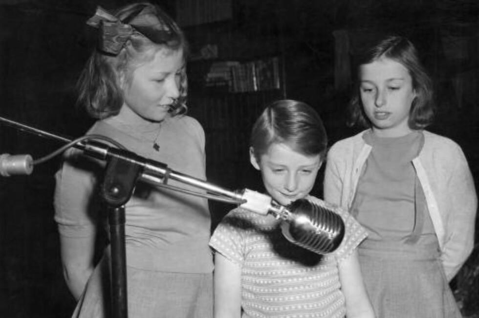 I VIRKELIGHETEN:  Kronprinsbarna Astrid, Harald og Ragnhild kringkaster sin julehilsen fra Amerika julen 1942. Foto: NTB Scanpix