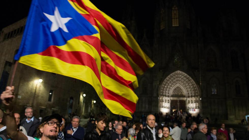 VIL UT AV SPANIA:  En spanjol vaier med det katalanske flagget i Barcelona i går kveld. I dag stemmer et stort antall katalanere for å løsrive seg fra Spania, til den spanske regjeringens store irritasjon. Statsministeren i Spania kaller dagens uoffisielle folkeavstemming for meningsløs, og ber innbyggerne ta til vettet. Foto: Paul Hanna/Reuters/Scanpix
