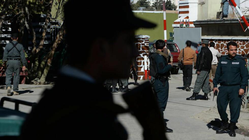 SIKRER ÅSTED:  Afghanske politifolk står vakt utenfor inngangen til politi-hovedkvarteret i Kabul. En selvmordsbomber klarte å komme seg inn, i morgentimene, og drepte en høytstående politimann. Foto: Marai Shah/Afp/Scanpix