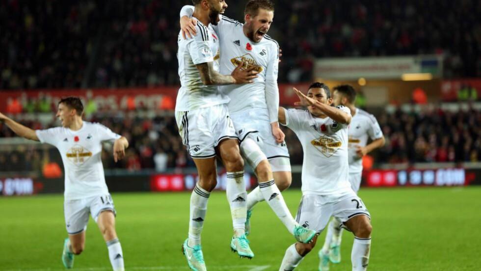 TRE POENG: Swansea brukte tre minutter på å sette to mål - nok til å ta hjem alle tre poengene mot Arsenal. Her feires Gylfi Sigurdssons perle av et frisparkmål. Foto. EPA/DIMITRIS LEGAKIS
