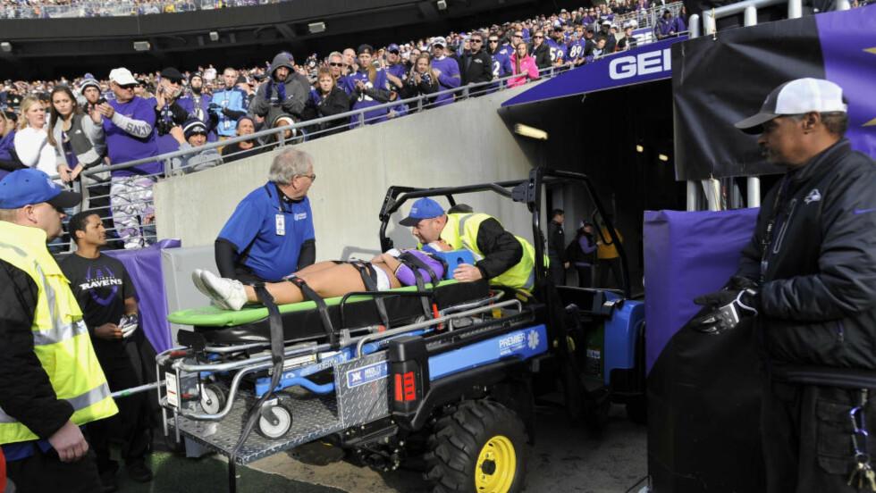 FRAKTET UT FRA STADION:  Baltimore Ravens-cheerleaderen blir fraktet bort fra stadion etter det fatale uhellet. Foto: AP Photo/Gail Burton/NTB Scanpix.