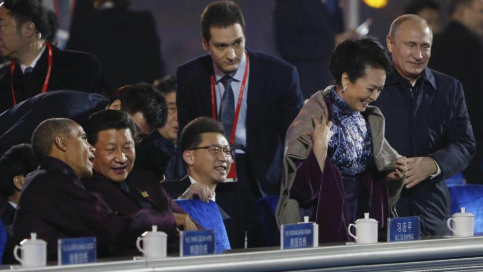 GOD TONE: Mens USAs president, Barack Obama, og Kinas president, Xi Jinping, snakket sammen, ga Russlands president, Vladimir Putin (t.h.) Kinas førstedame, Peng Liyuan, en jakke på så gallant vis at det ble sensurert av kinesiske myndigheter. Foto: AP Photo/Andy Wong