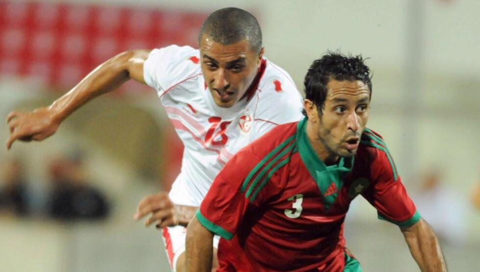 HIVES UT: Marokkos forsvarsspiller Adil Karroucay (t.h.) og hans lagkamerater får ikke muligheten til å spille i Afrikamesterskapet 2015. Marokko hives ut av mesterskapet etter å ha nektet å trekke sin søknad om å utsette mesterskapet. FOTO: AFP/FETHI BELAID