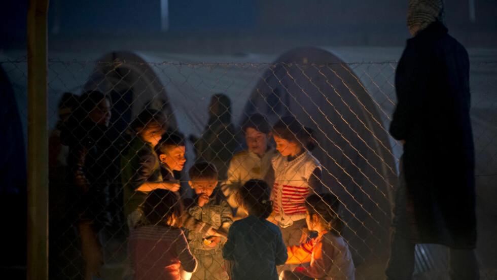 SYRISKE BARN: Kurdiske barn fra Syria varmer seg på et bål i en flyktningeleir i Suruc på grensa mellom Tyrkia og Syria. Foto: AP Photo/Vadim Ghirda