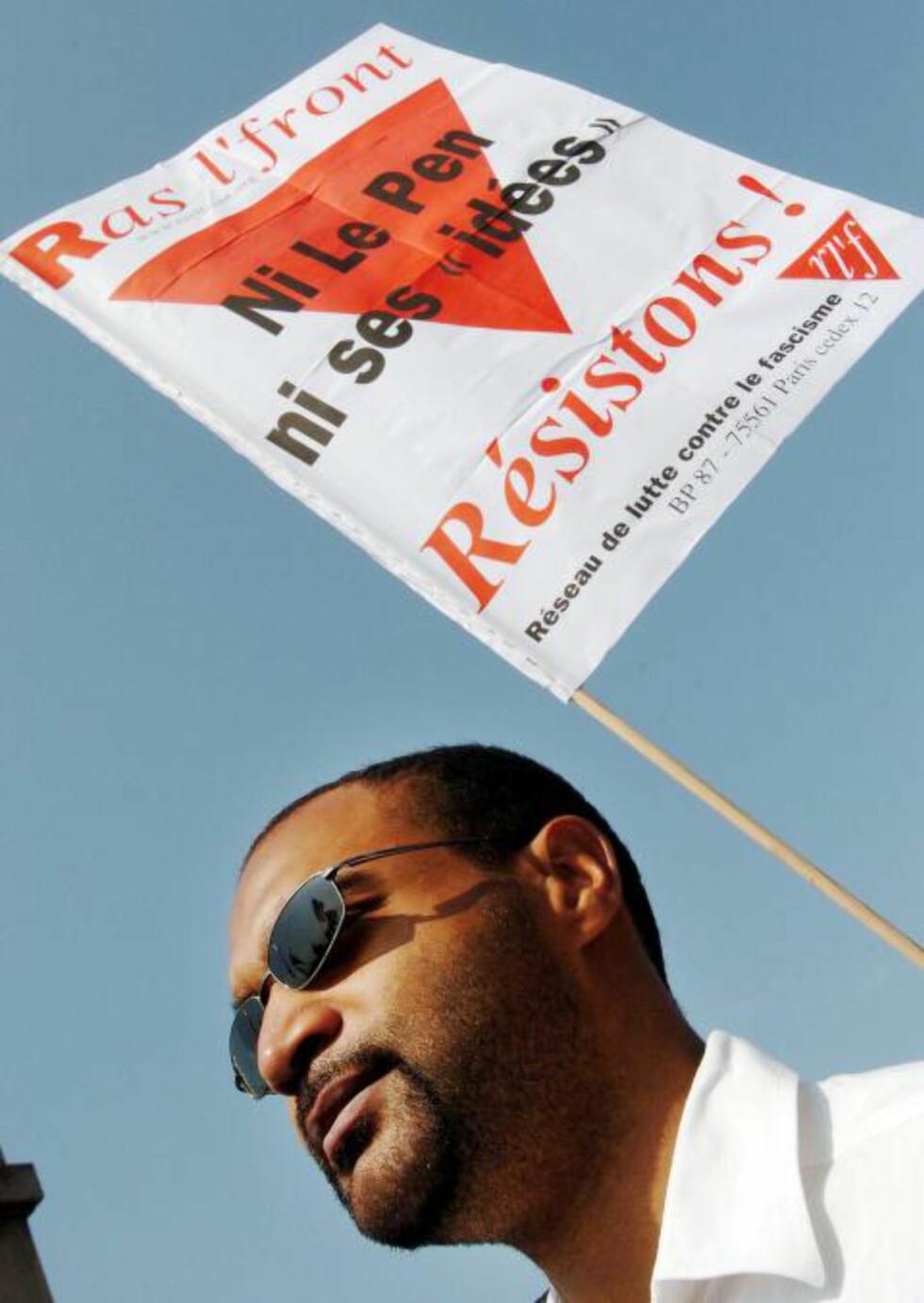 """KRASS KRITIKK: Dominique Sopo leder SOS Racisme. Den franske organisasjonen regnes som forgjengeren til de andre europeiske SOS Rasisme-bevegelsene. På plakaten står det """"Ikke Le Pen, ikke hans ideer, gjør motstand"""". Foto: JEAN AYISSI/AFP"""
