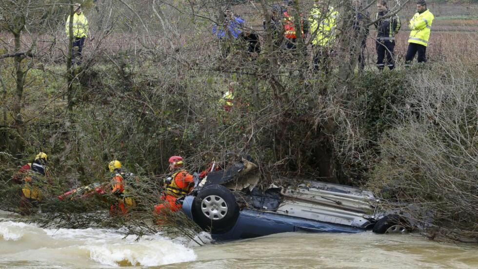 TRAGISK ULYKKE: Redningsarbeidere jobber febrilsk for å redde familien på fire etter at bilen deres ble fanget i vannmassene fra en flomrammet elv nær Cruviers-Lascours i det sørlige Frankrike i dag. Foto: BORIS HORVAT / AFP