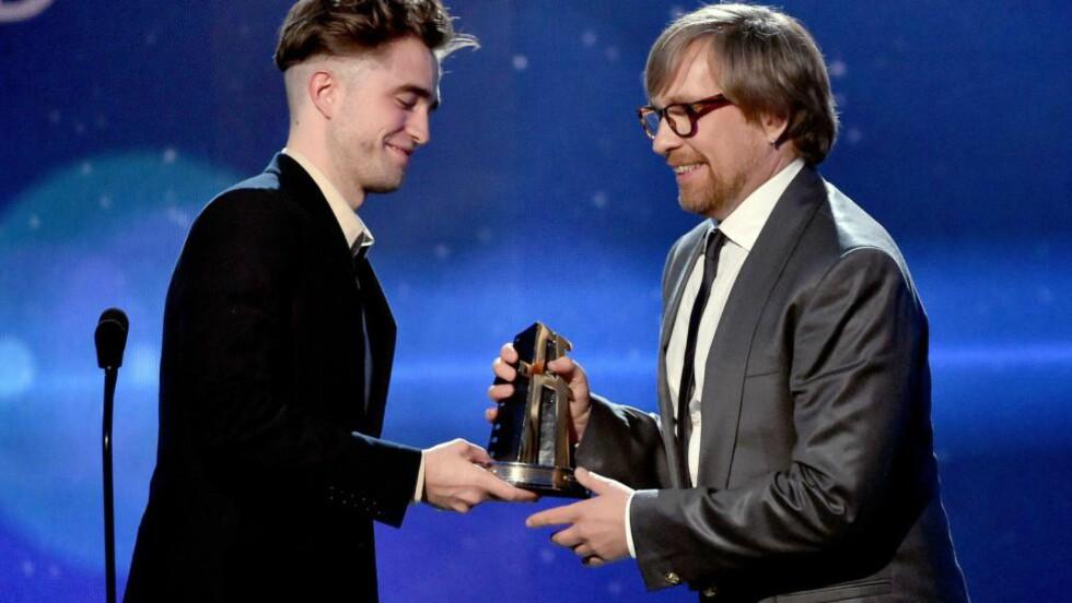 PRISVINNER: Robert Pattinson overrakte prisen for beste regi til Morten Tyldum under Hollywood Film Awards. Foto: AFP