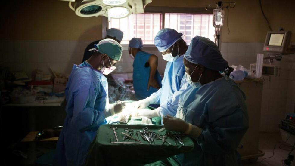 PÅ JOBB:  Legen Martin Salia (t.v) er med på en operasjon i Sierra Leones hovedstad Freetown. Sykehuset ble stengt 11. november, etter at Salia ble ebola-smittet. Han er nå på sykehus i USA. Foto: Mike DuBose/Epa/Scanpix
