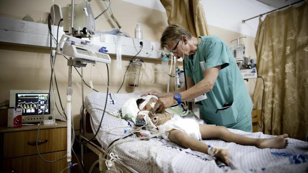 PÅ JOBB I GAZA:  Mads Gilbert undersøker et av de mange barna som ble skadd under den massive bombingen av Gaza i sommer. Foto: Tomm W. Christiansen / Dagbladet