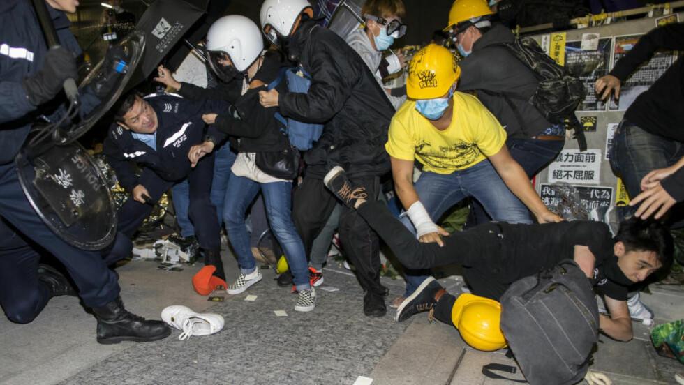 GATEKAMPER:  Politiet i Hongkong havnet i nok et gateslag med demokratiaktivister da en liten gruppe forsøkte å trenge seg inn i byens lovgivende forsamling onsdag. Foto: Reuters.
