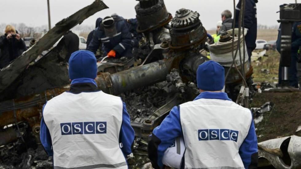 BESKUTT: Observatører fra OSSE, Organisasjone4n for Samarbeid og Sikkerhet i Europa, ser på mens redningsmannskaper samler vrakrestene etter det nedskutte flyet fra Malaysia Airlines, Rute 17, i Hrabove, i det området som opprørerne kontrollerer i Ukraina. Vrakrestene skal franktes med toh til byen Kharkiv, hvor Ukrainas regjering har makta. Nå har uniformerte personer skutt mot observatørene. Foto: AP / Scanpix / Mstyslav Chernov