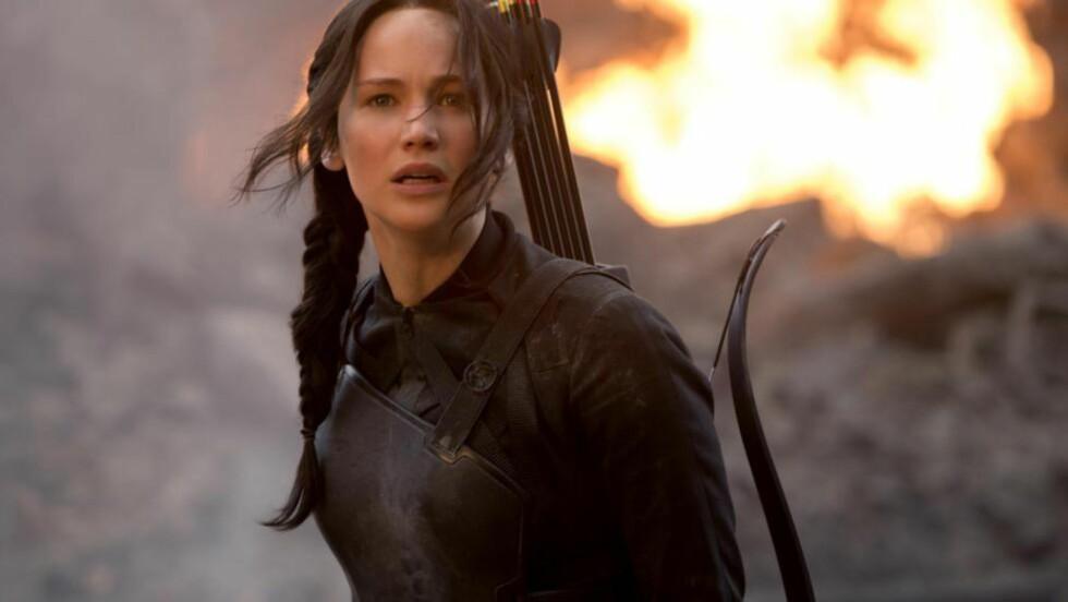 SKJERPINGS: Jennifer Lawrence i rollen som Katniss Everdeens i den nye «Hunger Games: Mockingjay Part 1» som nå skal trekke ungdommer til kinosalene, og forfatter Ida Jackson og litteraturviter Mari Wold Sannerud skriver i dag at anmeldere av denne typen filmer og litteratur må skjerpe seg kraftig. Foto: MURRAY CLOSE