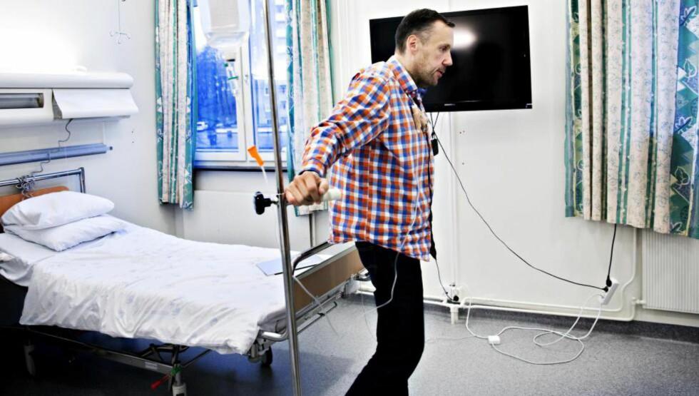 VENTETID: Bård Andersen har ligget på Ullevål sykehus siden august i påvente av å reversere fedmeoperasjonen. Inn i hovedpulsåren i halsen har han koblet intavinøs glykose for å unngå at blodsukkeret blir farlig lavt. -  Dette er blitt daten min, sier Andersen, der han leier stativet rundt. Foto: NINA HANSEN