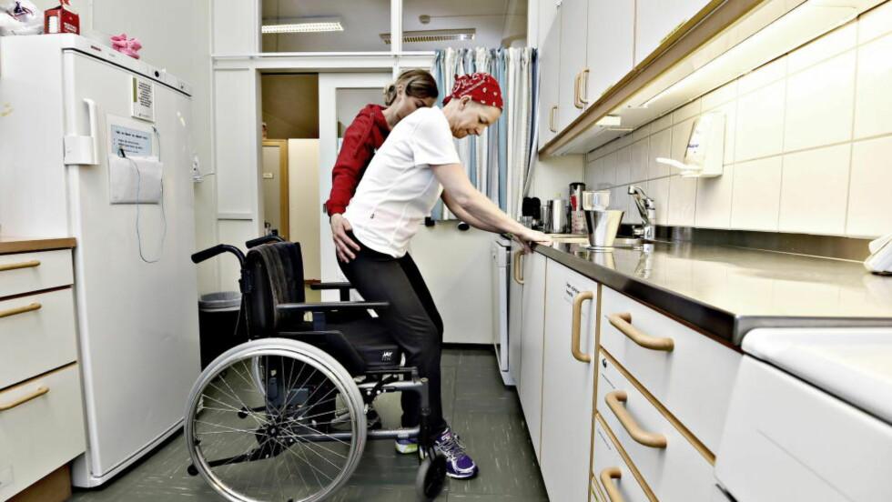 HARD TRENING: Sissel Wølner (49) fikk hjerneslag for tre uker siden. Nå er hun på opptrening på Sunnaas sykehus. Ergoterapeut Anne Gro Eckhoff hjelper mens Wølner trener på å hente glass ned fra hylla på øvingskjøkkenet. Foto: HANS ARNE VEDLOG