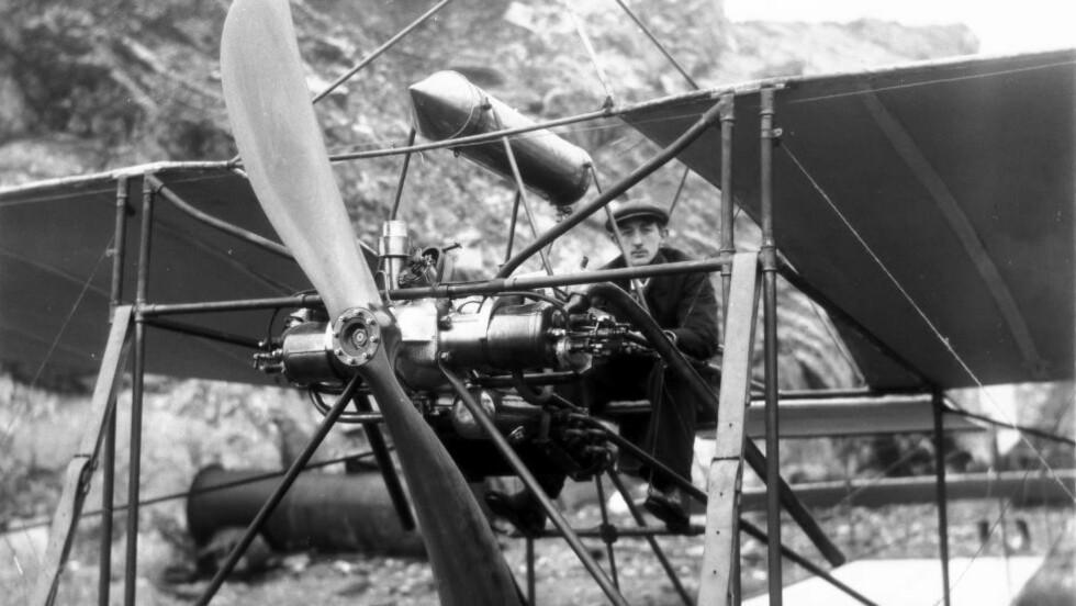 FØRSTEMANN: Einar Lilloe Gran i flyet han bygde, fotografert på ukjent sted i desember 1909. Den rakettformede gjenstanden over motoren er drivstofftanken. Den er plassert høyt fordi motoren måtte ha falltrykk til tilførselen. Foto: Foto: Anders B. Wilse / Norsk folkemuseum