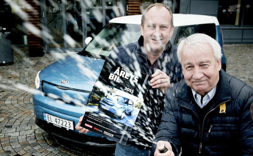 STORNORNØYD: Administrende direktør i Kia Bil Norge AS, Jan Pettersen, spretter gladelig champagnen da Rune M. Nesheim fra motorredaksjonen overrekker budskapet. FOTO: BJØRN LANGSEM