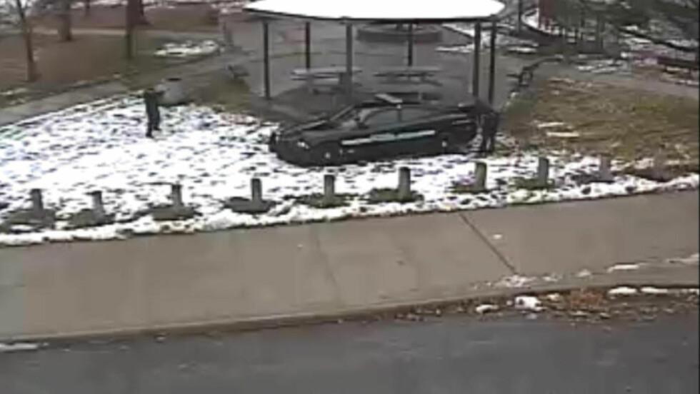 SKUTT: De to politifolkene på hver sin side av bilen, sekunder etter at politimannen til høyre på bildet har avfyrt to skudd mot Tamir Rice fra kort hold. Overvåkningsvideoen ble frigitt av politiet i Cleveland i dag. Foto: REUTERS/Cleveland Police Department